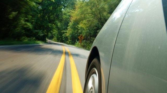 green hybrid car driving down road