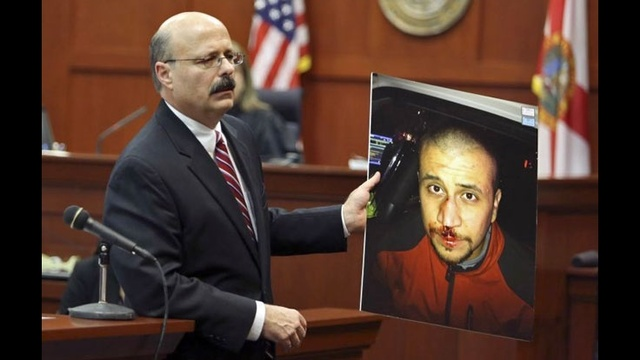 Bernie de la Rionda holds photo of George Zimmerman during closing arguments