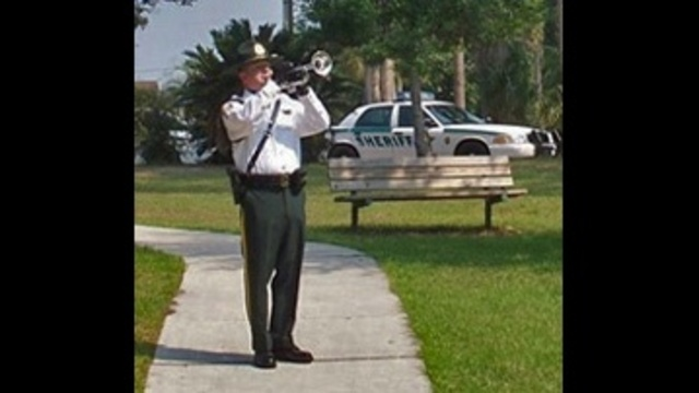 Detective David White playing taps
