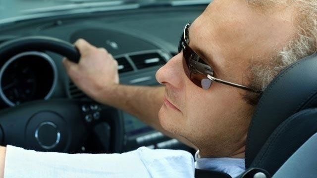 middle-aged man driving car in sunglasses