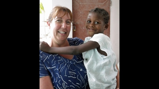 Tammy Hansen holds Haitian child
