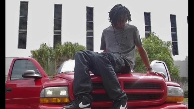 Tommie Stornes on hood of SUV_17581050