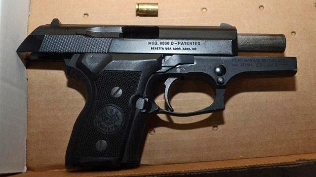 Gun in pawn store officer shooting_21279376