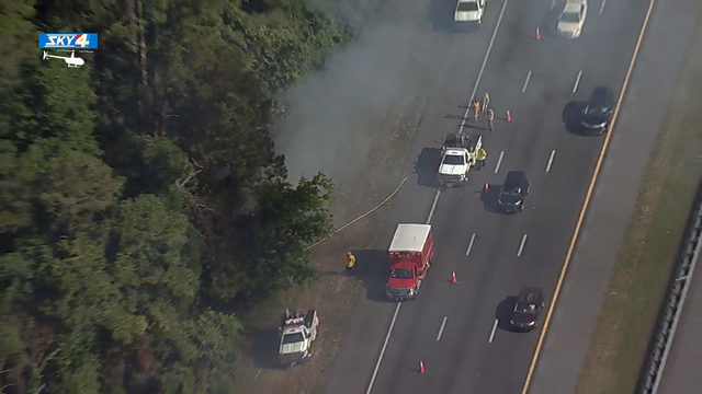 I-95 traffic flows past firefighters battling wildfire