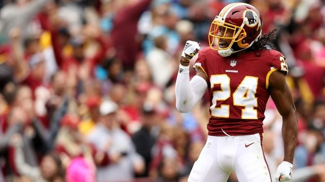 Redskins DB Norman runs with, jumps over the bulls