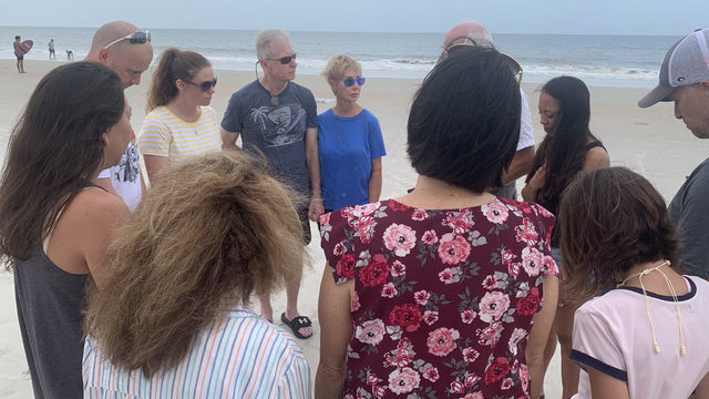Loved ones flood ocean & beach with prayers for firefighters stranded at sea